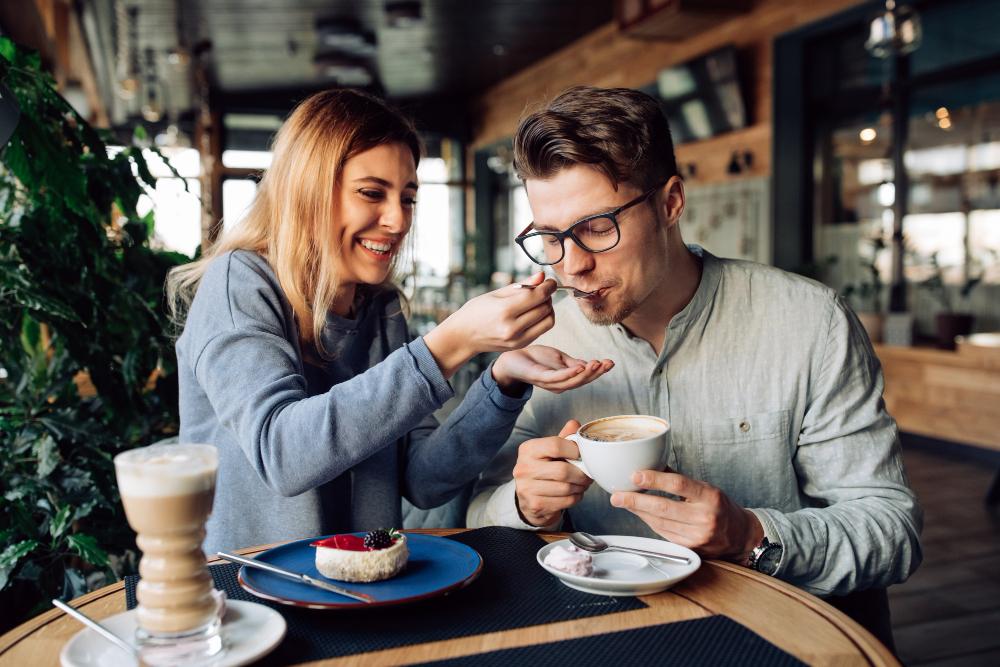 mujer sonriendo compartiendo comida con café acompañada de novio